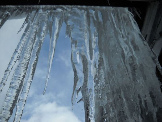 Photo by Roger Guggenheimer showing an icicle hanging from the school roof, depicting how cold it has been in McCloud.